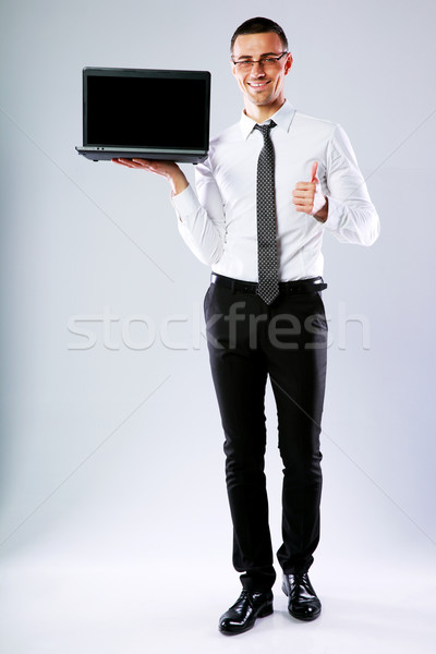 Businessman holding laptop and showing thumb up over gray background Stock photo © deandrobot
