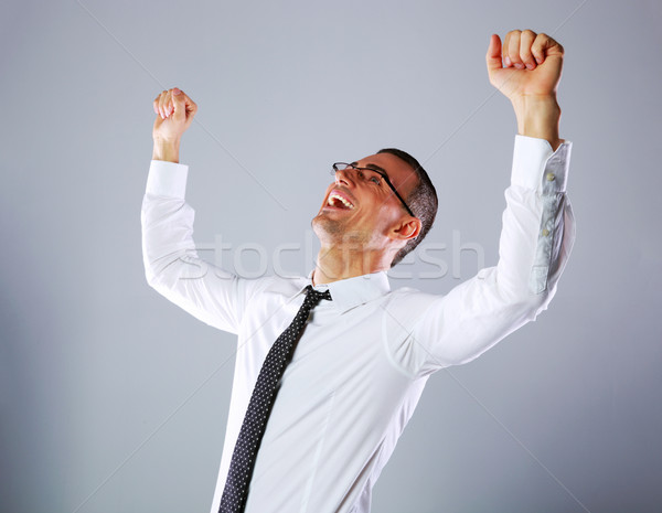 Portrait of a excited businessman on gray background Stock photo © deandrobot
