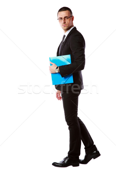 Side view portrait of a businessman in glasses with blue folder over white background Stock photo © deandrobot