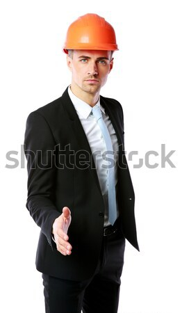 Confident businessman in helmet offering handshake over white background Stock photo © deandrobot
