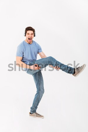 Happy sports man stretching on the mat over white background Stock photo © deandrobot