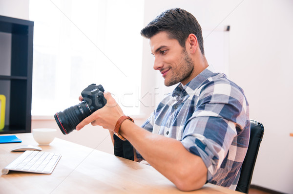 Happy man sitting at the table with photo camera Stock photo © deandrobot