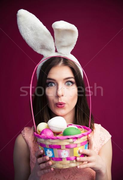 Aranyos fiatal nő húsvéti tojás kosár rózsaszín néz Stock fotó © deandrobot