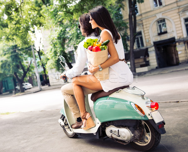 Happy young couple riding a scooter while woman holding a shopping bag full of groceries Stock photo © deandrobot