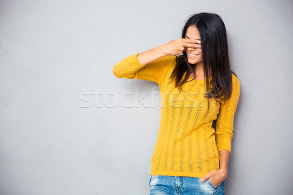 Woman covering her eyes with fingers Stock photo © deandrobot