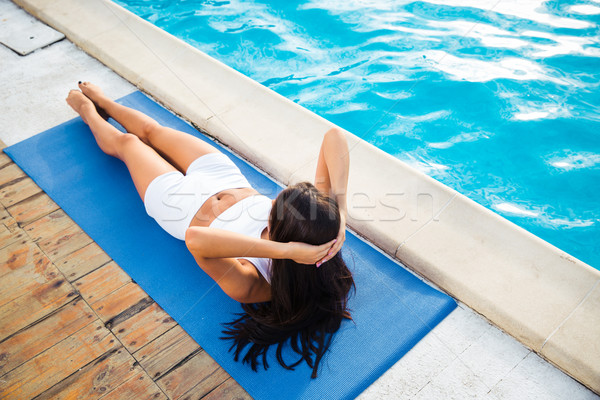 Woman working out on yoga mat outdoors Stock photo © deandrobot
