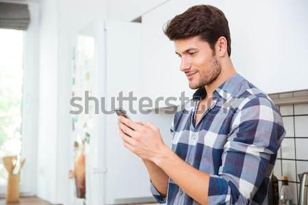 Handsome man looking in window Stock photo © deandrobot