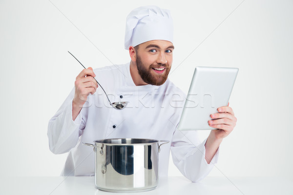 Male chef cook holding digital tablet and preparing food Stock photo © deandrobot
