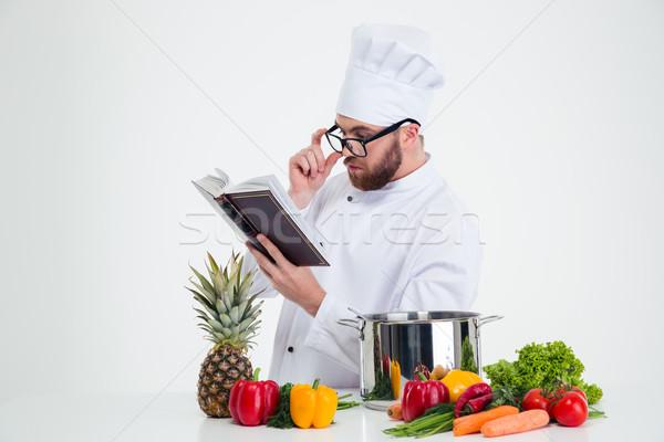 Chef cook in glasses reading recipe book Stock photo © deandrobot