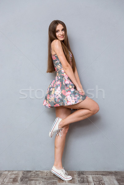 Playful pretty young woman posing on one leg Stock photo © deandrobot