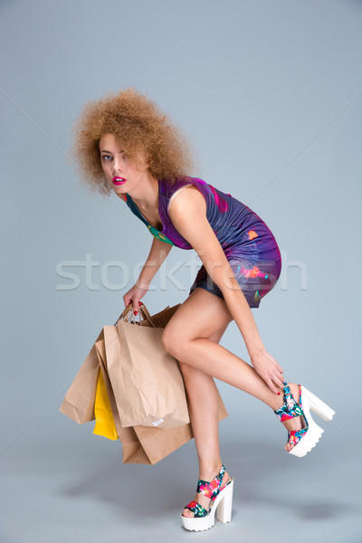 Exhausted woman touching her hurting legs on shopping Stock photo © deandrobot