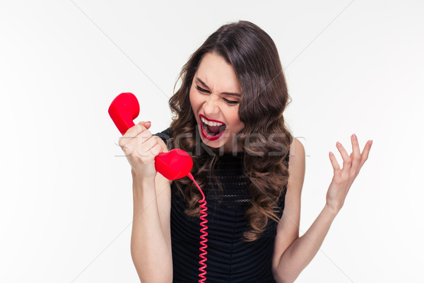 Crazy raged retro styled female shouting in red telephone receiver  Stock photo © deandrobot