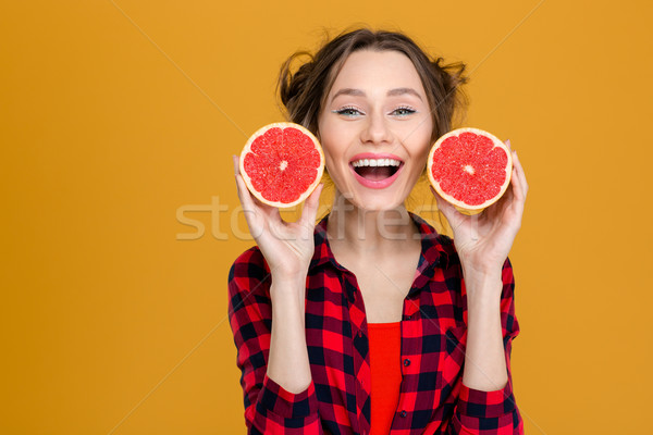 Smiling beautiful woman holding two halves of grapefruit Stock photo © deandrobot