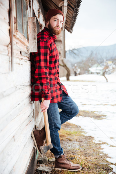 Man standing near old house in village and holding axe Stock photo © deandrobot