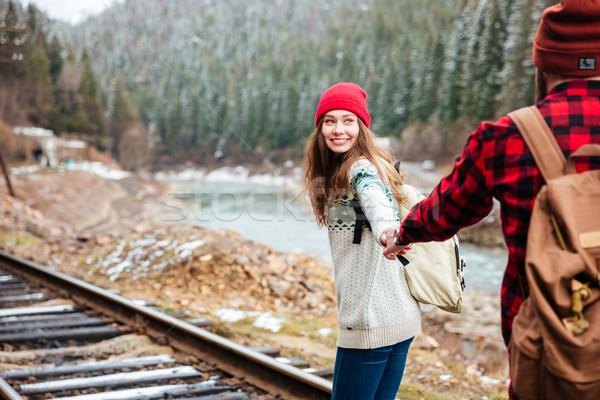 Happy young couple holding hands and walking along railway Stock photo © deandrobot