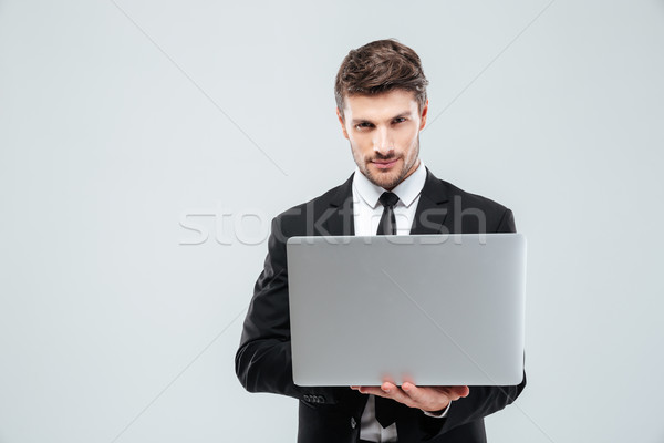 Confident young businessman in suit and tie using laptop Stock photo © deandrobot