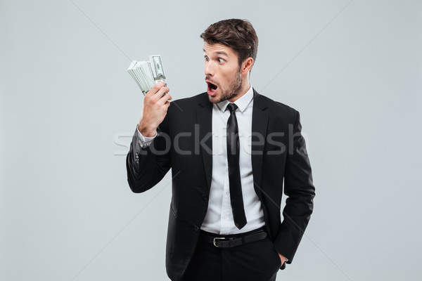 Shocked amazed young businessman standing and holding money Stock photo © deandrobot