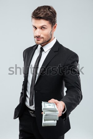 Confident young businessman giving money to you Stock photo © deandrobot
