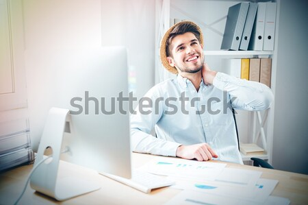 Happy relaxed young businessman in hat sitting and dreaming Stock photo © deandrobot