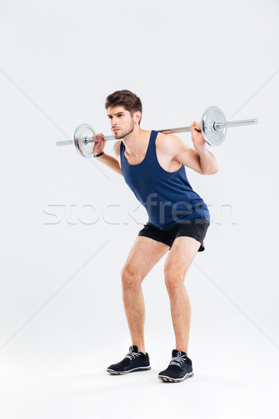 Attractive young sportsman holding barbell and doing squats Stock photo © deandrobot