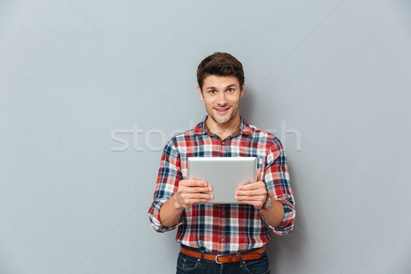 Smiling attractive young man in checkered shirt using tablet Stock photo © deandrobot