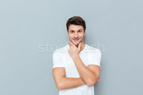 Handsome young pensive man standing and looking up Stock photo © deandrobot