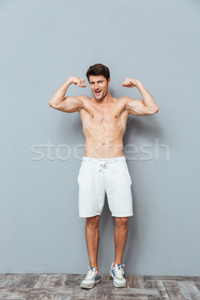 Cheerful attrative young man athlete standing and showing biceps Stock photo © deandrobot
