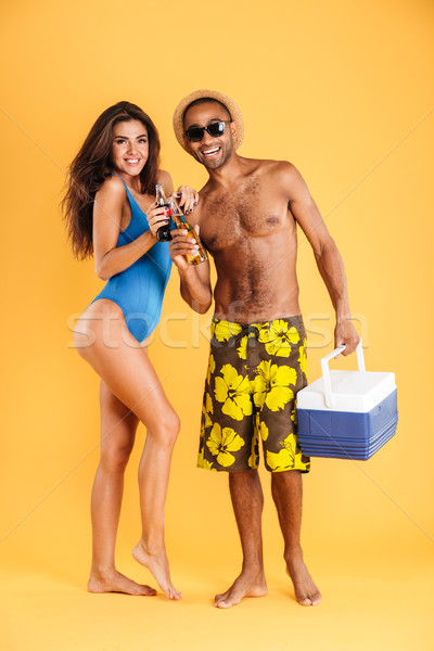 Couple holding glass bottles and cooler bag for picnic Stock photo © deandrobot
