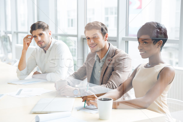 Business people sitting on training and making notes in office Stock photo © deandrobot