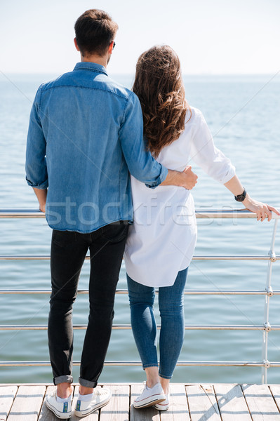 Full length of a young couple standing backwards hugging Stock photo © deandrobot