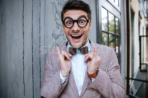 Cheerful funny young man in round glasses and wooden bowtie Stock photo © deandrobot