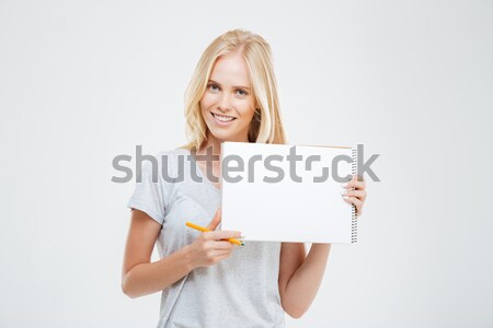 Laughing cheerful pretty girl showing blank notebook Stock photo © deandrobot