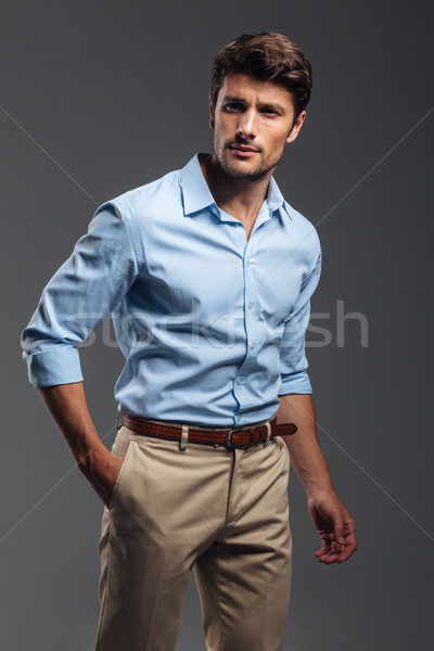 Handsome young man standing with hand in pocket Stock photo © deandrobot