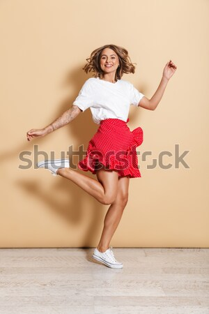 Cheerful young woman listening to music from mobile phone Stock photo © deandrobot