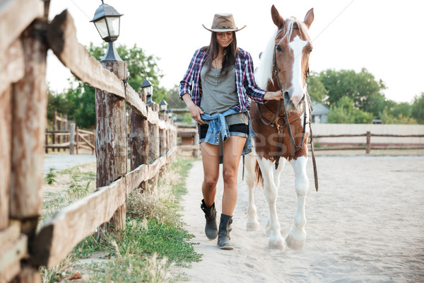 Woman cowgirl in hat walking with her horse in village Stock photo © deandrobot