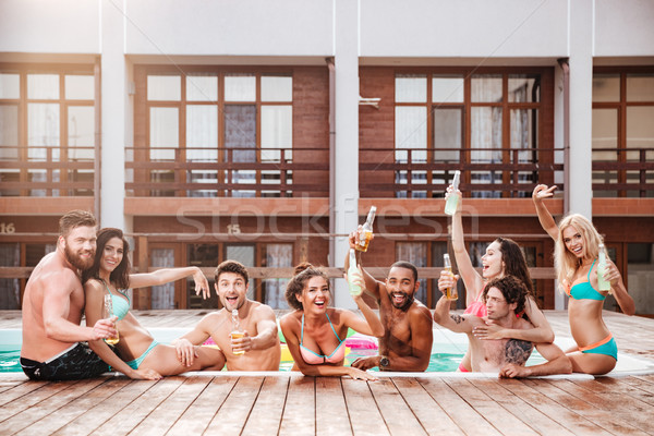 Croup of cheerful happy friends drinking beer at the pool Stock photo © deandrobot