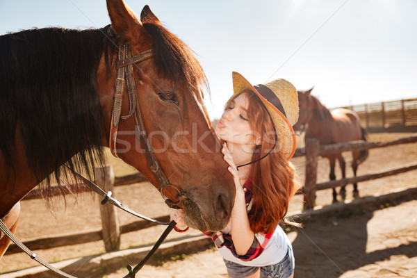 Stock photo: Cute woman cowgirl standing and kissing her horse