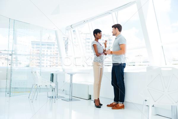 Dos jóvenes gente de negocios pie hablar oficina Foto stock © deandrobot