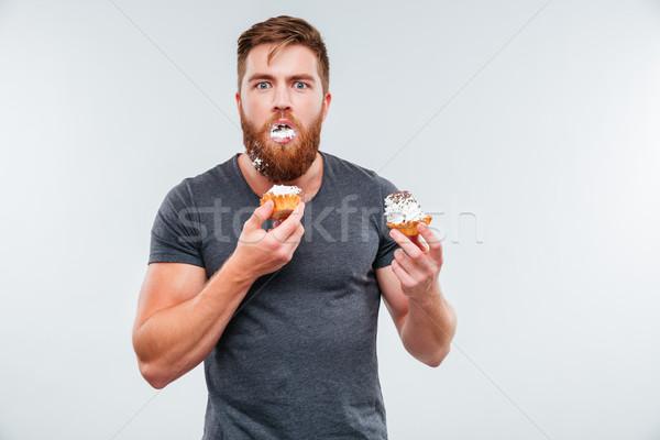 Mocskos szakállas fiatalember eszik krém torták Stock fotó © deandrobot