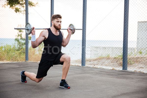 Konsantre genç sakallı spor adam halter Stok fotoğraf © deandrobot