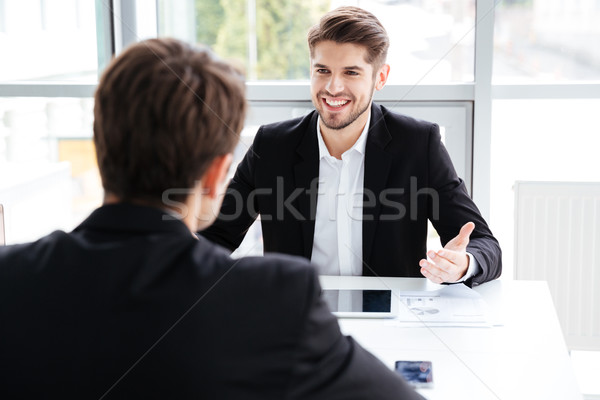 Two cheerful businessmen using tablet and working on business meeting Stock photo © deandrobot