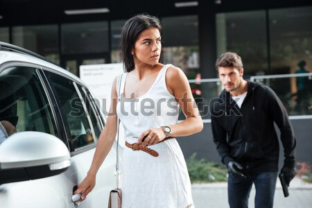 Pretty young woman being stalked by man criminal with gun Stock photo © deandrobot