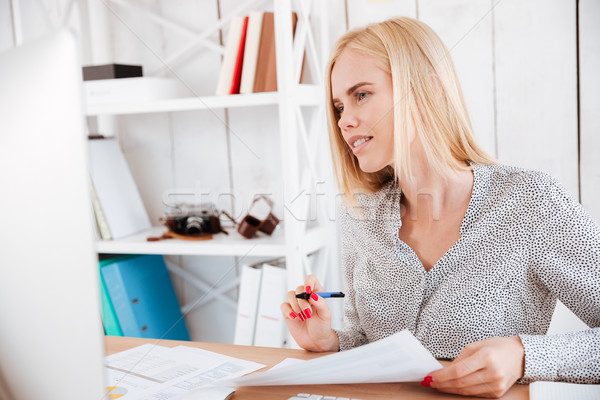 Casual young businesswoman making notes while looking at computer monitor Stock photo © deandrobot