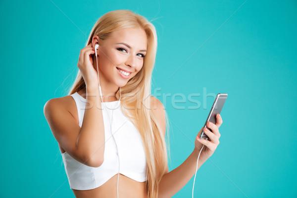 Fiatal csinos lány fülhallgató hallgat zene Stock fotó © deandrobot