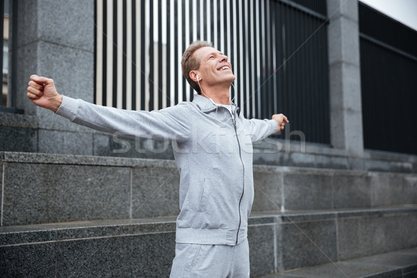 Happy Runner warming up on the street Stock photo © deandrobot