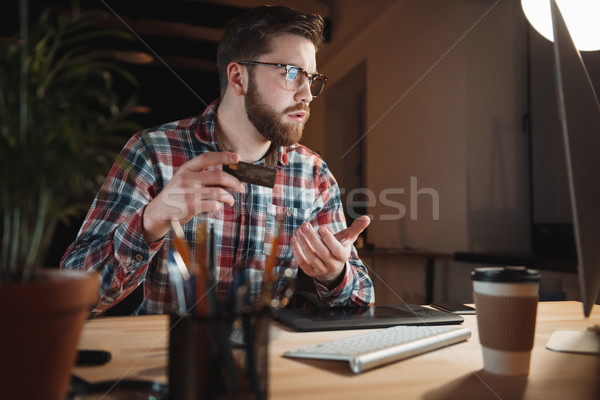 Serious casual businessman using credit card to buy things online Stock photo © deandrobot