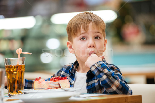 Boy eating cake and drinking juice in cafe Stock photo © deandrobot
