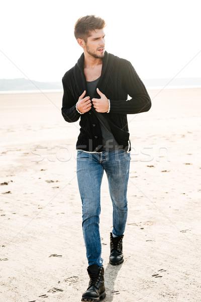 Casual man walking across the beach in the morning sun Stock photo © deandrobot