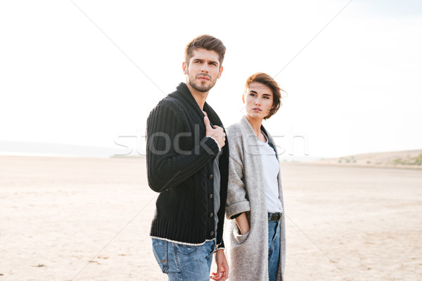 Young casual couple standing at the beach and looking away Stock photo © deandrobot