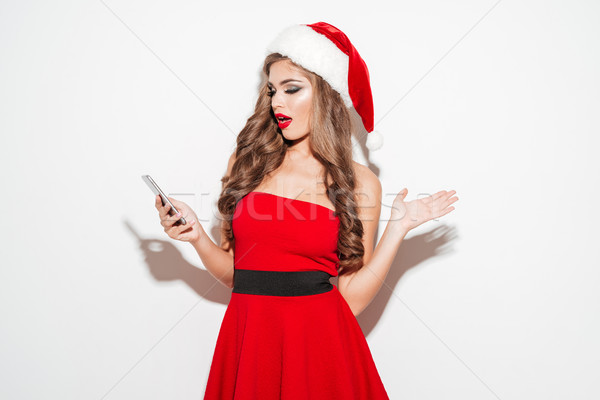 Surprised woman in red christmas outfit looking at mobile phone Stock photo © deandrobot